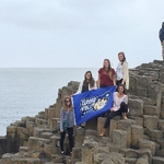 students at giants causeway with banner